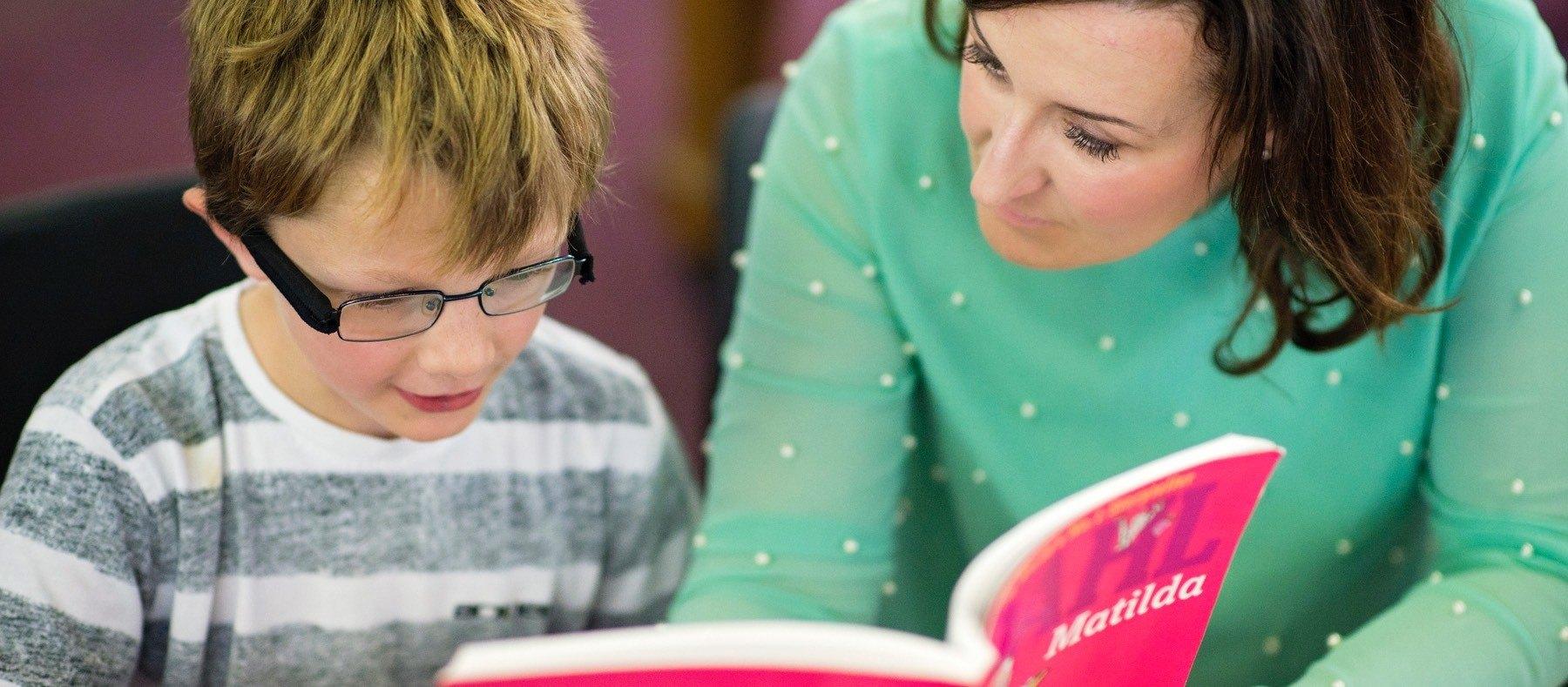 Key stage 1 Child reading the book matilda with VAKS tutor